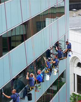 Seven men in Central Michigan providing high rise window cleaning services, suspended in bosun chairs, wearing blue shirts.