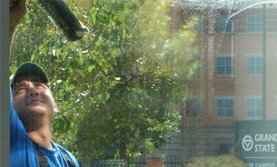 Commercial window cleaning by man in blue shirt using squeegee, cleaning GVSU building, downtown Grand Rapids, MI