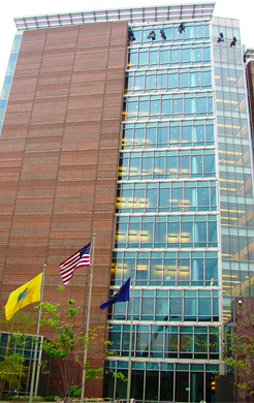 High rise window cleaning.  Three flags in front: middle is U.S. Flag, right is the Michigan flag.