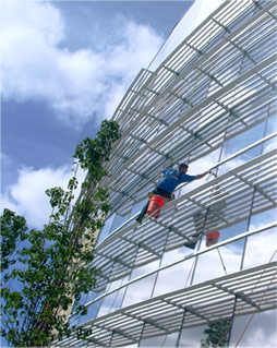 Professional window cleaning by man on 5-story building, suspended, on bosun chair washing windows