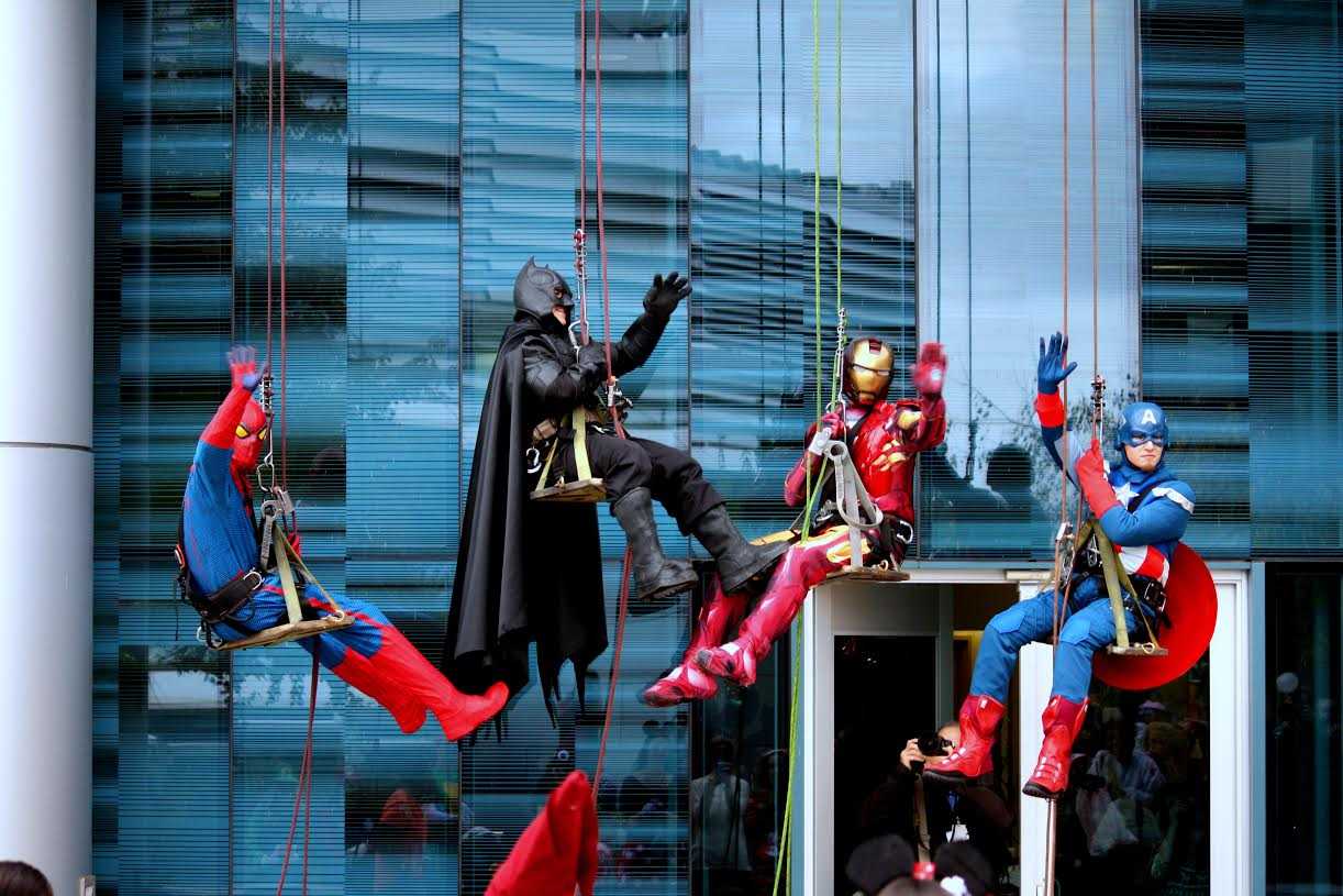 Superheroes pose for a photo op while repelling down the side of the hospital