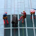 Superheroes waving at kids inside Helen Devos Children's Hospital