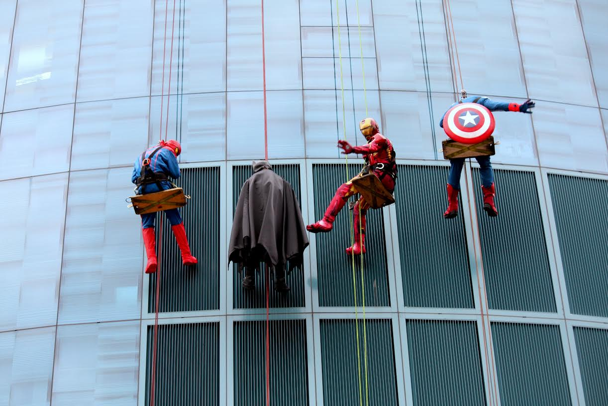 Superheroes waving at kids inside Helen Devos Children's Hospital