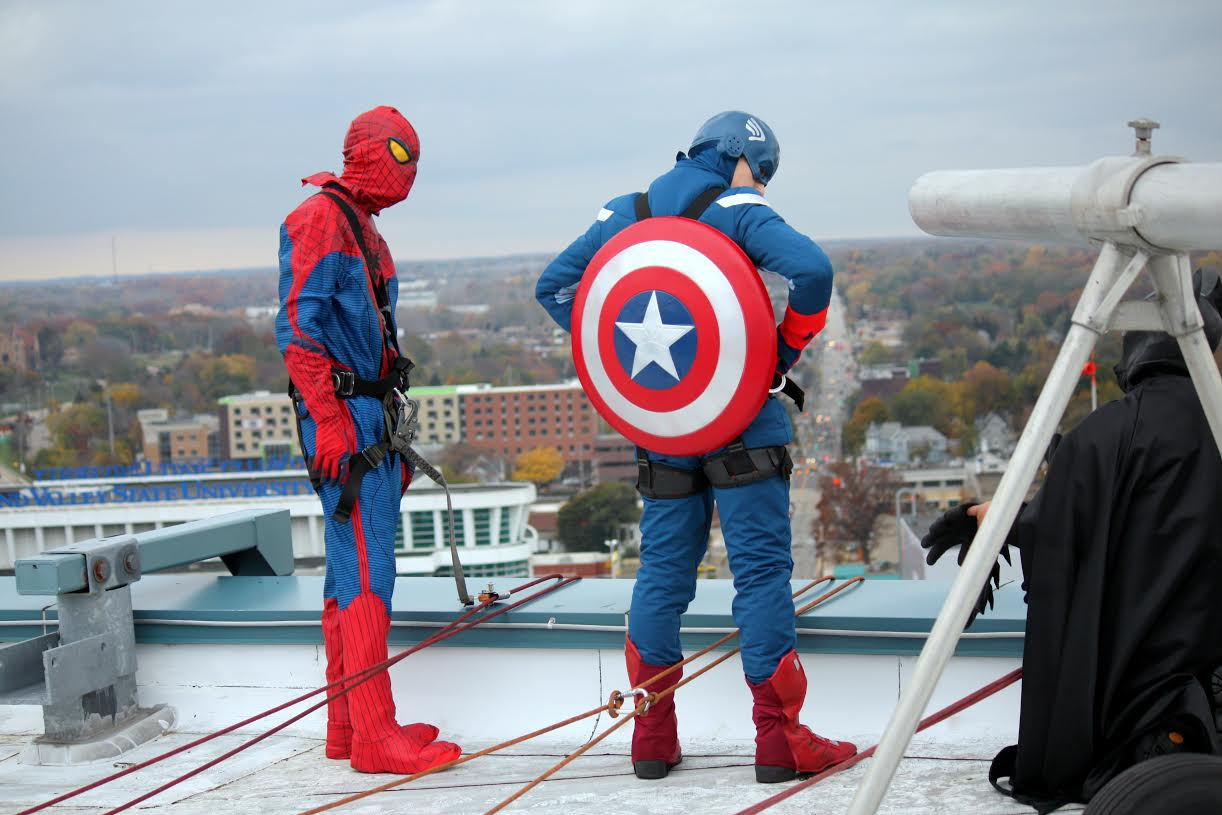 Spiderman and Captain America prepare to rappel down the side of the Helen Devos Children's Hospital