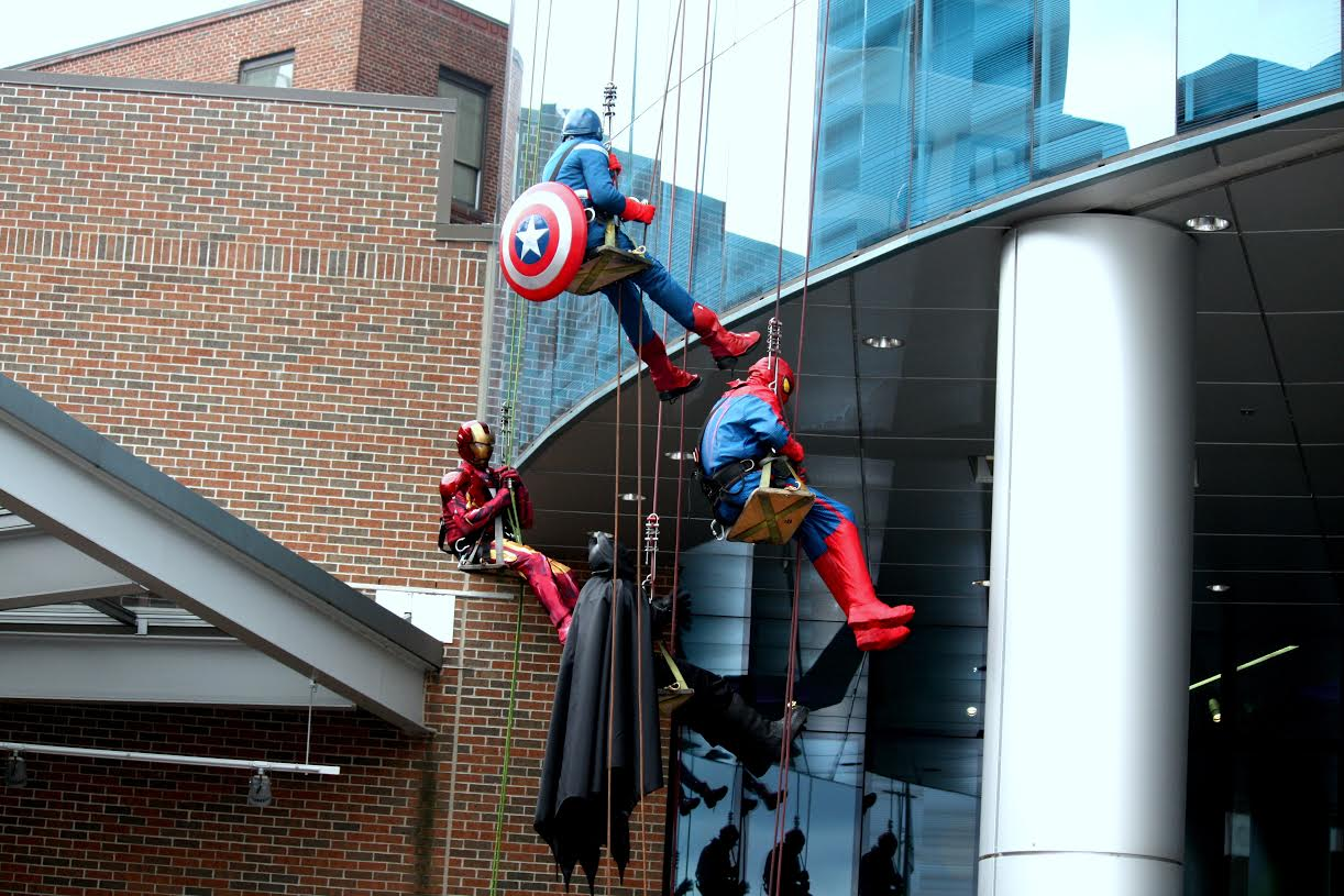 Batman, Spiderman, Captain America, and Ironman making their final descent down the Helen Devos Children's Hospital